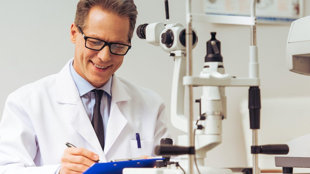 Handsome middle aged ophthalmologist making notes and smiling while sitting in his office; blog: Practice Solutions Beyond Medical Billing